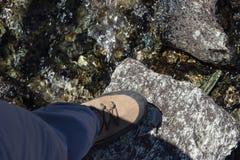 Брод Hiker поток скалистой горы с очень используемый trekking boots Стоковое Фото