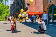 Бруклин, Нью-Йорк, США - 19-ое мая 2019: Человек принимая изображениям девушку, возможно дочь, с Афро-американским ферзем с желты стоковое фото