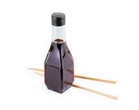 брызгает изолированных соевого соуса и палочек на белизне деревянный c Стоковые Изображения