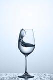 Брызгать волну более чистой воды в рюмке пока стоять на стекле с задрапировывает против светлой предпосылки стоковое изображение