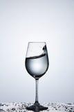 Брызгать прозрачную волну воды в бокале пока стоящ на стекле с капельками против светлой предпосылки стоковая фотография