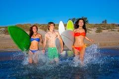Брызгать пляжа предназначенной для подростков группы серферов идущий стоковое изображение