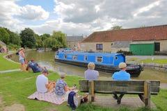 Брэдфорд на Эвоне, Великобритания - 13-ое августа 2017: Люди наслаждаясь летним днем на причале канала с красочными баржами на ка Стоковое Изображение