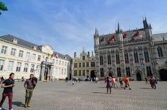 Брюгге, Бельгия - 11-ое мая 2015: Турист на квадрате Burg с здание муниципалитетом в Брюгге Стоковое Фото