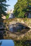 Брюгге - посмотрите к каналу и старому маленькому мосту Стоковое Изображение