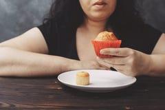 Брюзгливая женщина выбирая между маленькой и большой булочкой Стоковые Изображения RF