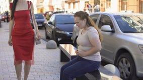 Брюзгливая женщина смотря завистливо на тонкой красивой даме проходя мимо на улицу, диету сток-видео