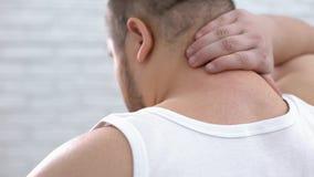 Брюзгливая мужская чувствуя боль шеи, массажируя мышцы, хребтовая болезнь, проблема здоровья стоковые фотографии rf