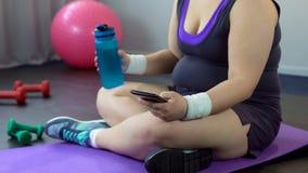 Брюзгливый спорт app скроллинга дамы на ее smartphone, наблюдая потеря веса приводит к стоковое фото rf