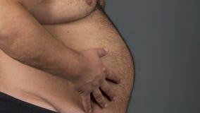 Брюзгливый тучный мужчина с большим животом на серой предпосылке, концепции диеты, здравоохранении видеоматериал