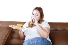 Брюзгливая женщина есть высококалорийную вредную пищу Стоковое фото RF