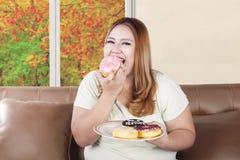 Брюзгливая женщина есть donuts Стоковые Изображения