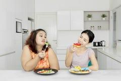 Брюзгливая женщина ест салат и друг ест donuts Стоковая Фотография