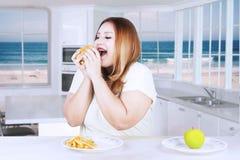 Брюзгливая женщина решая съесть высококалорийную вредную пищу Стоковые Фото