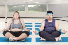 Брюзгливые люди размышляя в йоге класса стоковое фото rf