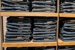 Брюки джинсов на витрине магазина Штабелированные джинсы собрания джинсовой ткани голубых джинсов Стоковые Фото