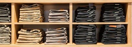 Брюки джинсов на витрине магазина Штабелированные джинсы собрания джинсовой ткани голубых джинсов Стоковая Фотография RF