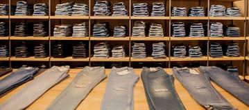 Брюки джинсов на витрине магазина Штабелированные джинсы собрания джинсовой ткани голубых джинсов Стоковая Фотография