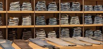 Брюки джинсов на витрине магазина Штабелированные джинсы собрания джинсовой ткани голубых джинсов Стоковое Изображение