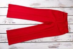 Брюки моды красные на белой деревянной предпосылке стоковое фото