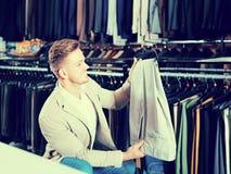 Брюки мужского клиента рассматривая в магазине одежды men's Стоковое фото RF