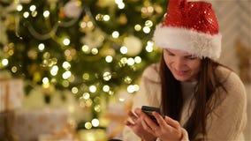 Брюнет в шляпе Санты печатая на ее мобильном телефоне и усмехаясь на рождественской елке предпосылки Девушка в крышке Xmas исполь