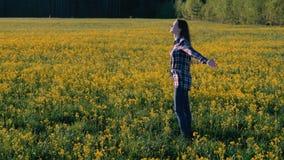Брюнет женщины идет на поле желтых цветков Простирания и дышают глубоко видеоматериал