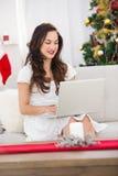 Брюнет используя ее компьтер-книжку на кресле Стоковая Фотография