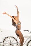 Брюнет идя на езду велосипеда на пляже Стоковая Фотография