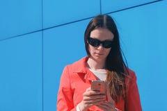 Брюнет молодой женщины в солнечных очках в красном пальто ждет кто-то и проверяет ее телефон, отправляя СМС стоковая фотография rf