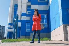 Брюнет молодой женщины в солнечных очках в красном пальто ждет кто-то и проверяет ее телефон, отправляя СМС стоковая фотография