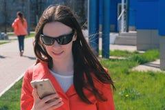 Брюнет молодой женщины в солнечных очках в красном пальто ждет кто-то и проверяет ее телефон, отправляя СМС стоковые изображения