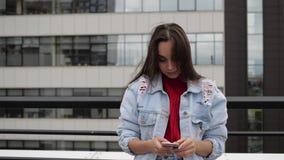 Брюнет на крыше печатая в телефоне сток-видео