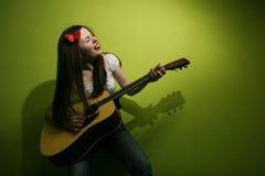 Брюнет одичало играя гитару Стоковое фото RF