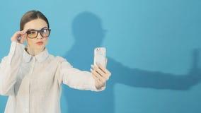 Брюнет принимает Selfie Smartphone на голубой предпосылке в студии Привлекательный носить девушки битника модный сток-видео