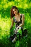 Брюнет сидя на зеленой траве стоковые фотографии rf