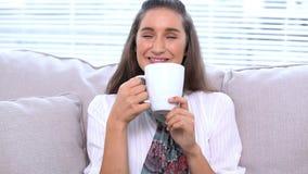Брюнет сидя на софе выпивая ее чашку сток-видео