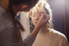 Брюнет составляет женщину художника применяясь для того чтобы компенсировать br брюнет стоковое изображение