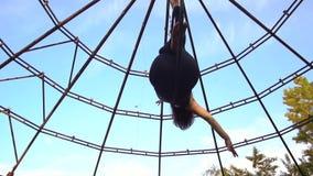 Брюнет спорт кладет в кольцо для воздушной акробатики и смотрит к небу куда птицы летают акции видеоматериалы