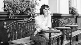 Брюнет стороны макияжа женщины мечтательный ест предпосылку террасы кафа торта Гастрономическая наслаждение r Девушка ослабляет стоковая фотография