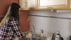 Брюнет с длинными волосами в рубашке шотландки освобождает затор в раковине с плунжером сток-видео