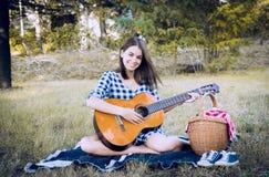 Брюнет усмехается на камере пока играющ классическую гитару стоковая фотография