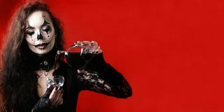 Брюнет Хеллоуин-стиля нося черные одежды льет красную жидкость которая выглядит как кровь в форме череп стеклянное блюдо Пробел стоковое изображение