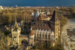 Будапешт, Венгрия - вид с воздуха красивого замка Vajdahunyad в парке города на заходе солнца с темными облаками Стоковое Изображение RF