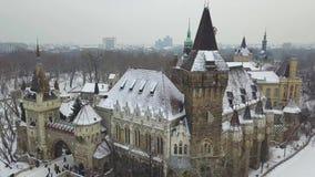 Будапешт, Венгрия - воздушный отснятый видеоматериал 4K принимать трутня на замка Vajdahunyad в снежном парке города видеоматериал