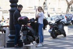 Будапешт, Венгрия - 9-ое апреля 2018: Полнометражный портрет молодого привлекательного положения пар на улице города около мотоци стоковое фото