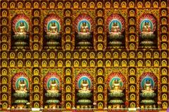 Будда отображает на стене в виске стоковое изображение