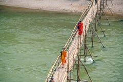 Буддийские монахи пересекая бамбуковый мост Стоковое Изображение