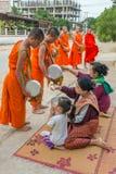 Буддийские монахи собирая милостыни в утре в Vang Vieng, Лаосе Стоковые Изображения