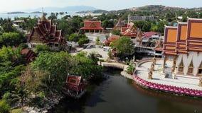 Буддийский висок около озера Взгляд сверху трутня крыш и статуй чудесного буддийского виска расположенного около озера на солнечн видеоматериал